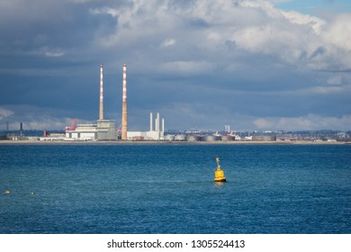 Blue sea industrial seascape under a dramatic sky with the Flue-gas stacks/chimneys of a decommissioned waste incinerator in the distance and a yellow buoy. Poolbeg peninsula in Dublin, Ireland.