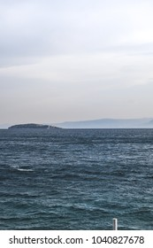 Blue sea with an island in the horizon in Greece.