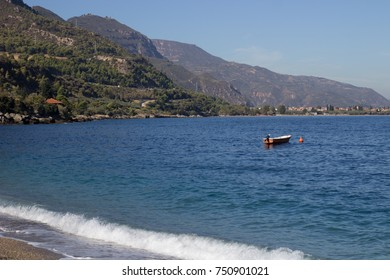 blue sea and a little boat on the water with forest on the background and small waves crashing on the beach