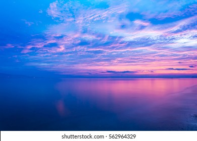 Blue sea and a moving reflection of sunlight . White sandy beach on vacation at sunset