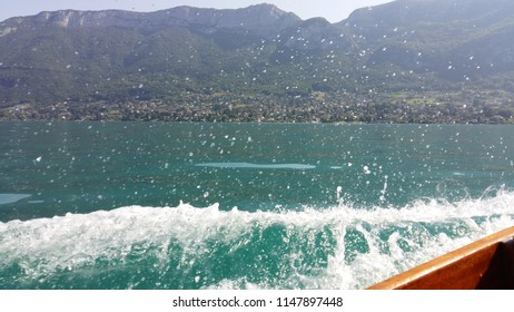 Blue sea with prop wash wake and Annecy's mountains in horizon. Annecy, France.