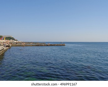 Blue sea and sky, people relax on the beach and piers, boats on horizon