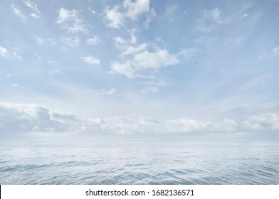 Blue sea and sky. White clouds. Hardly visible horizon line. Seascape. Abstract nature background
