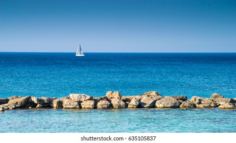 Blue sea with stones and white sailing vessel at background, Cyprus