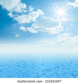 Blue sea, sun and clouds on sky
