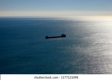 Blue sea in the sunlight in the morning and a large cargo ship