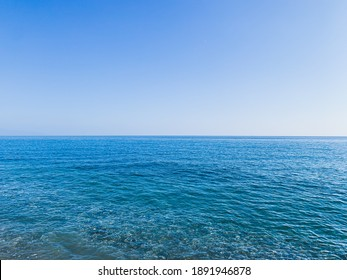 Blue sea surface and clear blue sky
