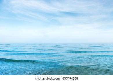 Blue sea water with waves and white clouds on the sky. Calm tropical landscape