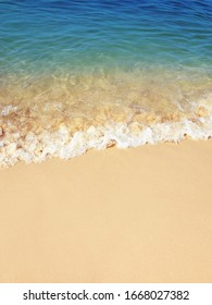 Blue sea wave with white foam on the golden sand beach. Summer holidays concept, tropical island vacation. Tourist travel backdrop, card or banner template with copy space - Shutterstock ID 1668027382