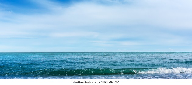 Blue sea with waves with sea foam under cloudy blue sky with white clouds in sunny day, beautiful nature landscape with horizon line