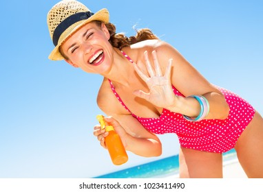 Blue sea, white sand paradise. smiling modern woman in colorful red swimwear on the seacoast applying sun cream