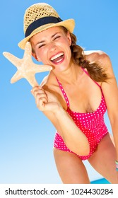 Blue sea, white sand paradise. happy modern woman in colorful red swimwear on the seashore showing starfish