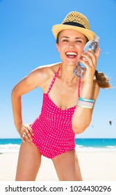 Blue sea, white sand paradise. Portrait of happy young woman in colorful red swimsuit on the beach enjoying cold water
