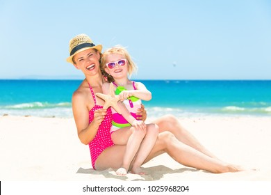 Blue sea, white sand paradise. smiling young mother and child in colorful swimwear on the beach showing starfish