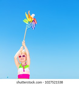 Blue sea, white sand paradise. Full length portrait of happy modern girl in colorful swimsuit on the seashore holding colorful windmill toy