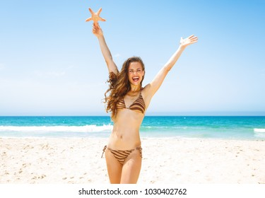 Blue sea, white sand paradise. smiling young woman with long brunette hair in beachwear on the seacoast holding starfish rejoicing
