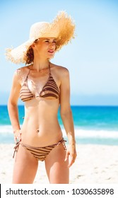 Blue sea, white sand paradise. young woman in bikini and beach straw hat on the seashore looking into the distance