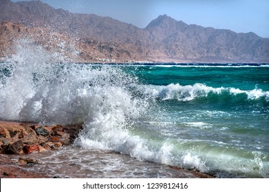 Blue sea with white waves. Coast with swash and mountains on the background. Windy day in Dahab.