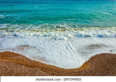 The blue of the sea.Pebble beach, the Wave.Sea foam on the rocks.