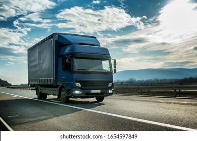Blue semi trailer truck on a highway driving at bright sunny sunset. Transportation vehicle