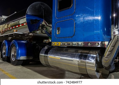 Blue semi truck with tanker trailer and chrome fuel tanks and exhaust pipes