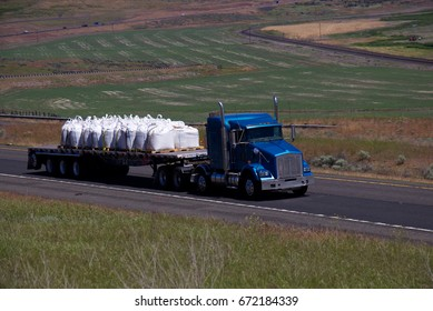 A blue semi-truck pulls a loaded flatbed trailer along the highway. June 20th, 2017 Oregon, USA