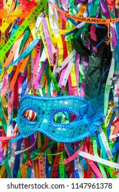 Blue sequined carnival mask in a background of Brazilian wish ribbons Salvador Bahia Brazil. Translation: Memory of Our Lord of Bonfim