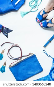 Blue set of woman fashionable clothes and accessories, top view. Blue outfit flat lay with female legs in pumps, handbag, jacket, jewelry and belt, top view. Fashion layout. Shopping or sale concept
