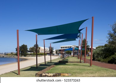 Blue shade sails  provide shelter at the  swimming beach  at Jetty baths and boat harbour from the cycleway  in Bunbury Western Australia on a fine late spring morning .
