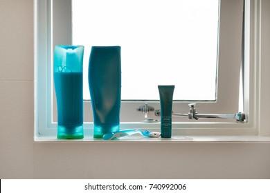 blue shampoo and conditioner bottles on bathroom window ledge