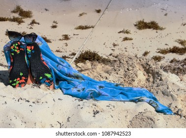Blue shawl and other personal belongings left on a tropical beach.