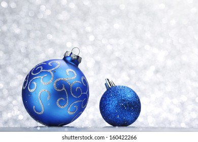 Blue shiny christmas balls on silver glitter background