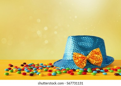 Blue shiny party Hat next to colorful candies on yellow wooden table