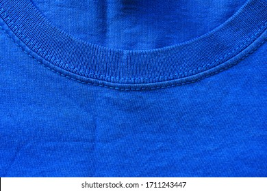 Blue shirt detail. Round collar neck worn shirt. Simple plain blue color clothes, wrinkled old blue sweater fragment
