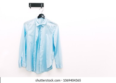 Blue shirt hanging on the white wall