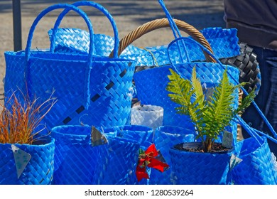 Blue shopping bags, shopping baskets, and flower pot holders made from upcycled packaging strap materials on a market stall