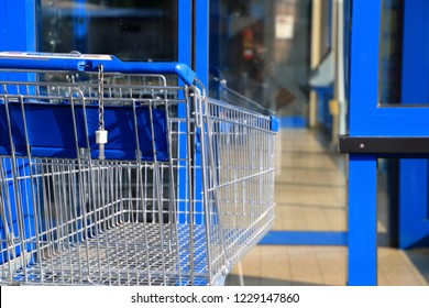 Blue shopping cart, trolley in front of an shop door