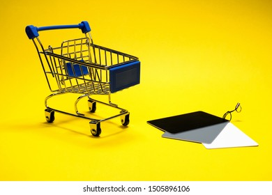 Blue shopping cart and white balance check card on a yellow background. Souvenir stroller for a supermarket at a photo shoot. Shopping concept for the photographer.