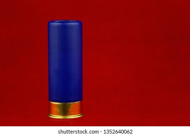 Blue shotgun cartridge isolated against a red background