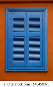 Blue shutters on an orange wall, in Plaka, Athens