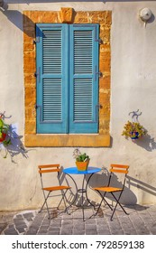Blue shutters window and beautiful small chairs and a table on sidewalk in Cyprus
