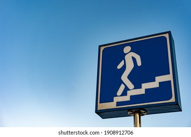A blue sign of entrance to the underpass. symbol for subway metro station. European traffic underpass walk sign, man walking down the stairs