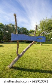 Blue sign made of wood with green grass and blue sky in background