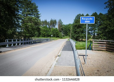 """Blue sign with name of the river """"Rospuda"""" by the road and bridge, Poland"""