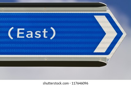 Blue sign pointing east