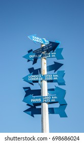 blue sign that shows distances to different parts of the world on Signal Hill in St. John's, Newfoundland, Canada, North America