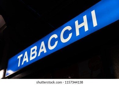Blue signage of a Tabacchi, Italian for Tobacco shop, on a black background. Also called a tobacco shop, a tobacconist's shop or a smoke shop, it is a retailer of tobacco products