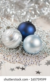 Blue and silver Christmas balls on a white wooden background