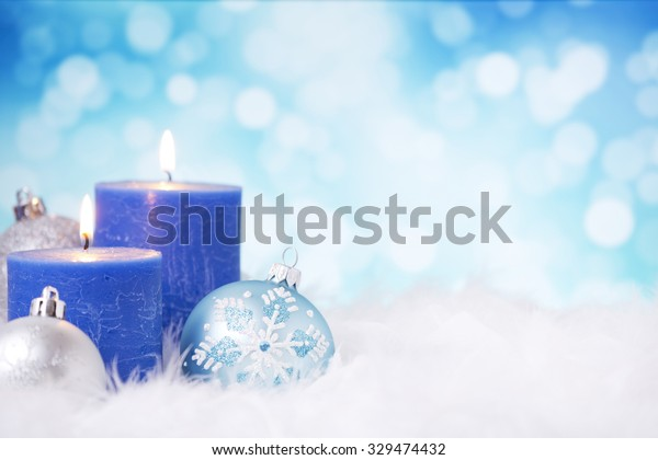 Blue and silver Christmas baubles and candles on a soft feathery surface in front of defocused blue and white lights.