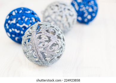 Blue and silver Christmas spheres on a white surface